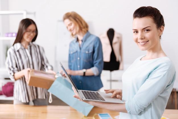Affascinante donna bruna che tiene un laptop e guarda davanti con un ampio sorriso felice mentre, sullo sfondo, i suoi colleghi imballano una scatola nella borsa