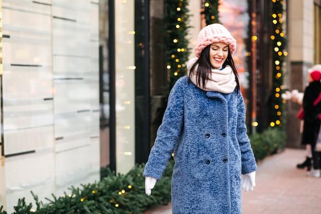 Affascinante donna bruna indossa un berretto rosa chiaro lavorato a maglia e una sciarpa che cammina per la città decorata con ghirlande. spazio per il testo