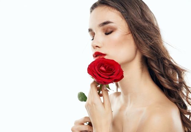 Affascinante donna bruna con spalle nude e un fiore profumato vicino al viso. foto di alta qualità