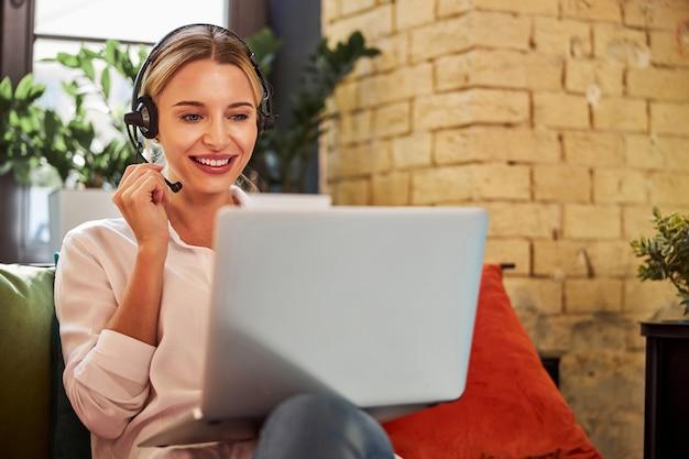 Affascinante donna d'affari in cuffia che parla con il partner commerciale sul laptop