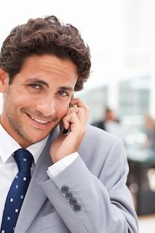Affascinante uomo d'affari telefonando nel suo ufficio