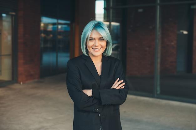 Affascinante donna d'affari con i capelli blu è in posa con le mani incrociate mentre guarda la fotocamera