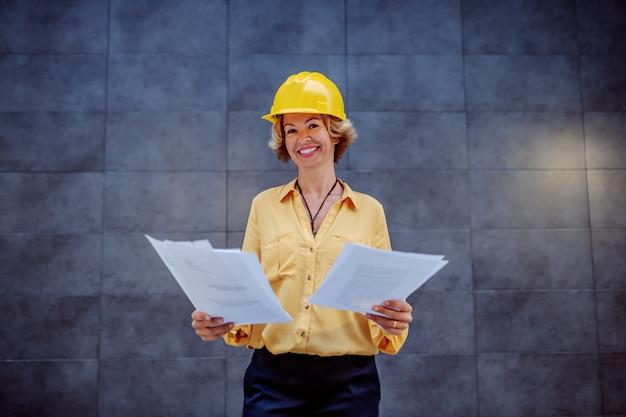 Affascinante architetto femmina senior bionda caucasica con i capelli corti e casco sulla testa in piedi all'aperto davanti al muro e in possesso di documenti importanti