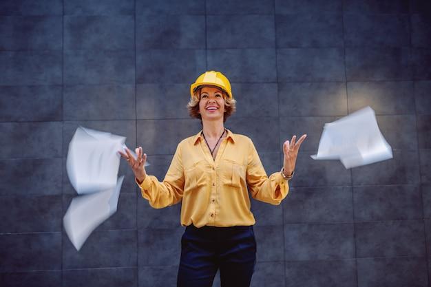Affascinante architetto femmina senior bionda caucasica con i capelli corti e casco sulla testa in piedi all'aperto davanti al muro e gettando in aria le carte.