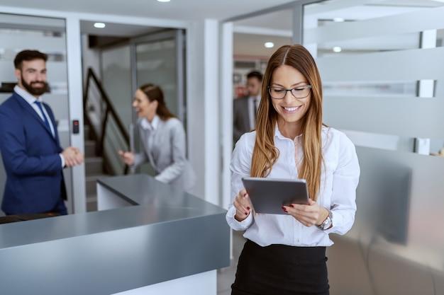Affascinante imprenditrice caucasica vestita in camicia e gonna in piedi sul corridoio e utilizzando tablet. sullo sfondo i suoi colleghi in piedi e in chat.