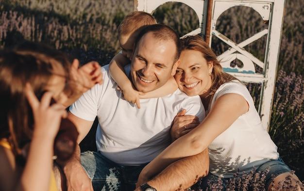 Affascinante famiglia caucasica seduto in un campo di lavanda in posa felicemente mentre si abbracciano