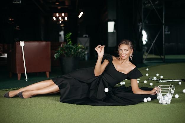 La signora caucasica affascinante posa per la macchina fotografica e gioca a golf, immagine isolata sul fondo scuro della sfuocatura