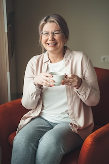 Affascinante donna caucasica senior con gli occhiali, bere un tè e sedersi sul divano