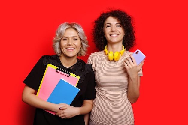 Affascinanti studenti caucasici con i capelli ricci sono in posa su una parete rossa con uno spazio vuoto in possesso di un cellulare e alcuni libri
