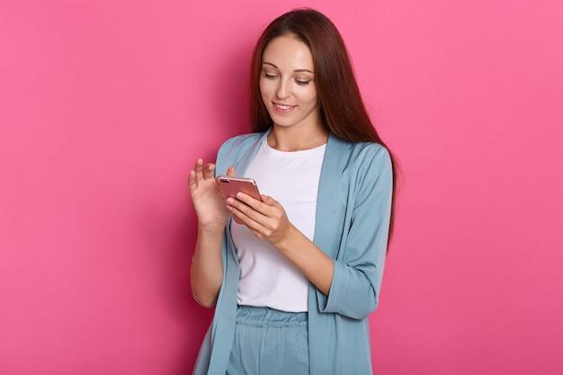 Affascinante giovane donna allegra che sorride sinceramente, usando il suo dispositivo, tenendo smartphone