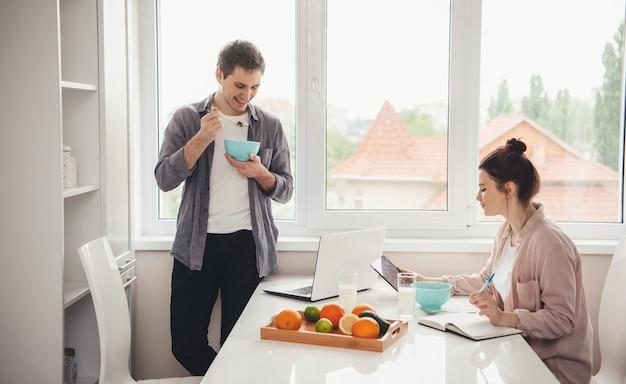 Affascinante coppia mangiare cereali con latte e fare lezioni online utilizzando tablet e laptop