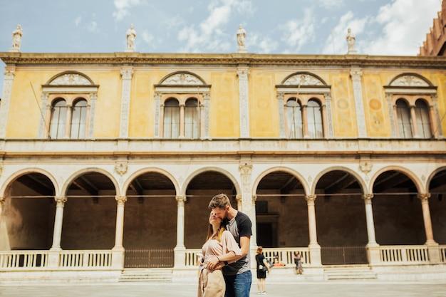 Affascinante coppia, uomo e donna, abbracciati dalle bellezze di verona.