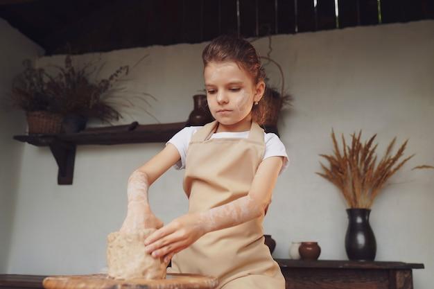 Affascinante bambina artigiana che gode di arte e produzioni della ceramica