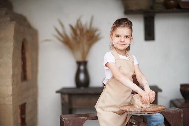 Bambina affascinante dell'artigiano che gode dell'arte e del processo di produzione delle terraglie