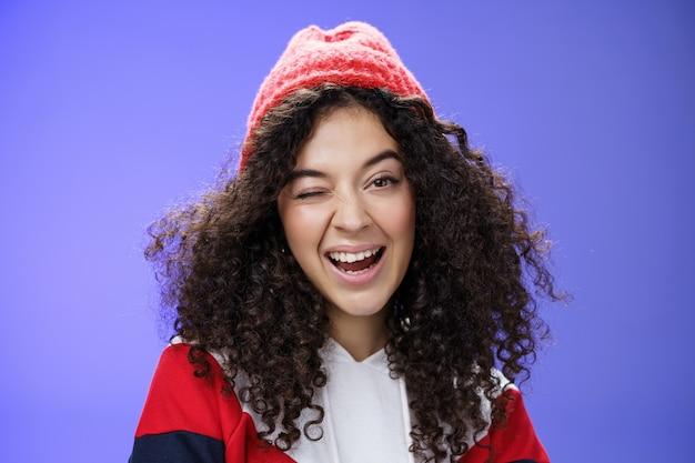 Affascinante donna carina che suggerisce di andare a giocare a palle di neve con lei che fa l'occhiolino con gioia mentre ci invita, sorride ampiamente indossando un elegante berretto rosso e una felpa mentre posa su sfondo blu.
