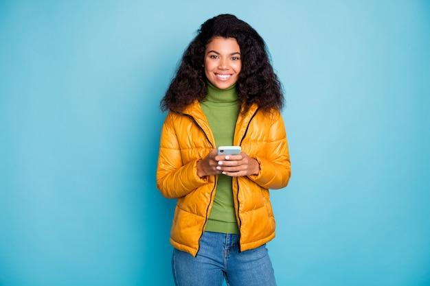 Affascinante pelle scura ondulata signora in possesso di telefono controllo abbonati buon umore indossare jeans giallo primavera soprabito maglione verde isolato muro di colore blu