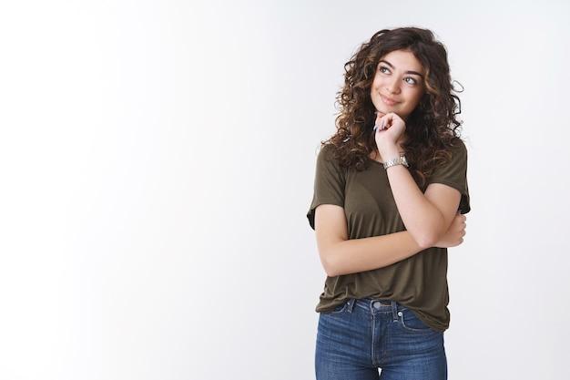 Affascinante sognante ragazza armena carina con i capelli ricci cercare toccare il mento sorridente sciocco ricordo bella bella memoria in piedi fantasticando su sfondo bianco godendo della finestra di vista dall'ufficio vacanza da sogno