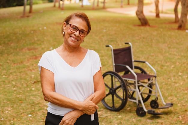 Affascinante donna anziana sorridente nel parco in piedi con la sedia a rotelle in