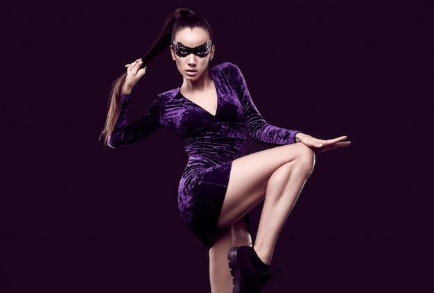 Affascinante donna bruna elegante in un bellissimo vestito viola e maschera di paillettes