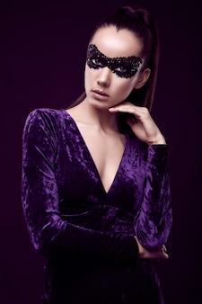 Affascinante donna bruna elegante in abito viola e maschera di paillettes