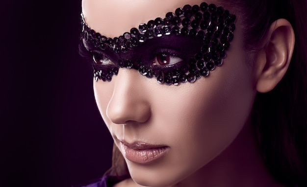 Affascinante donna bruna elegante nella maschera di paillettes