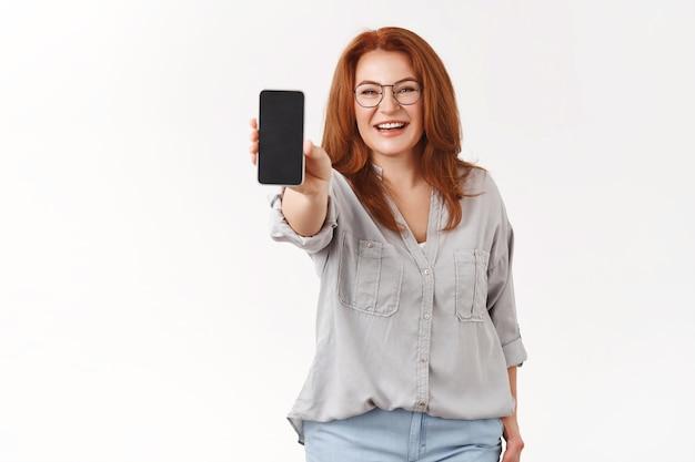 Affascinante, elegante, rossa, donna d'affari di mezza età, mamma, indossa gli occhiali, estendi il braccio, tieni premuto lo smartphone, mostra lo schermo del telefono, promuovono l'applicazione, muro bianco