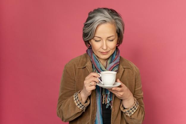 Affascinante donna elegante beve caffè o tè che tiene tazza bianca a guardarlo.
