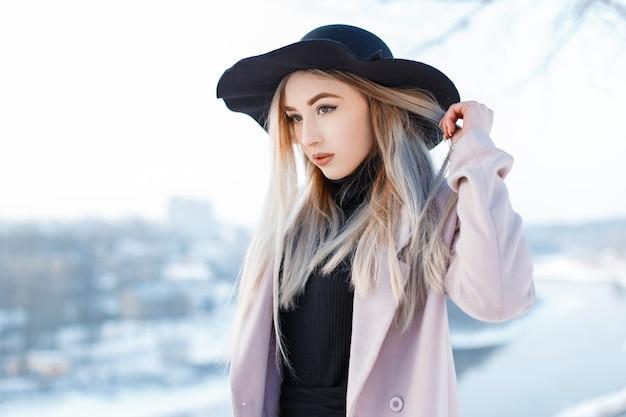 Affascinante giovane donna elegante in un cappello vintage in stile retrò in un cappotto rosa in un abito lavorato a maglia si trova in una calda giornata invernale