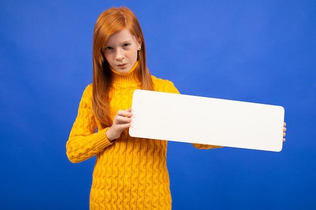 Adolescente dai capelli rossi europeo affascinante che tiene un'insegna da un foglio di carta per la pubblicità sul blu