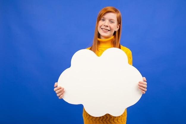 Adolescente dai capelli rossi europeo affascinante che tiene un'insegna da un foglio di carta con un modello per la pubblicità su un fondo blu dello studio