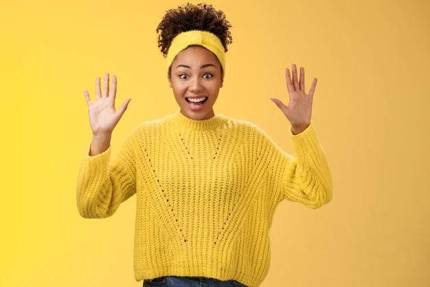 Affascinante eccitato sorridente amichevole millenaria ragazza afro-americana alzare le mani niente nascondere mostra palme alta resa in piedi divertito entusiasta sogghignando divertendosi in posa sfondo giallo.