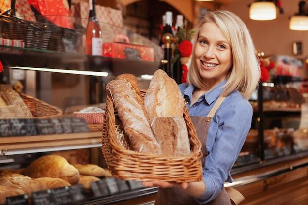 Affascinante panettiere femminile sorridente tenendo un cesto di pagnotte di pane appena sfornato. concetto di proprietario di panetteria
