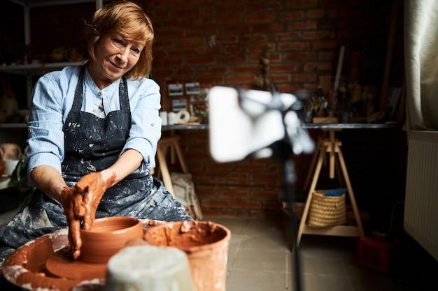 Affascinante vasaio femminile in grembiule che modella argilla e sorridente mentre fa la ceramica