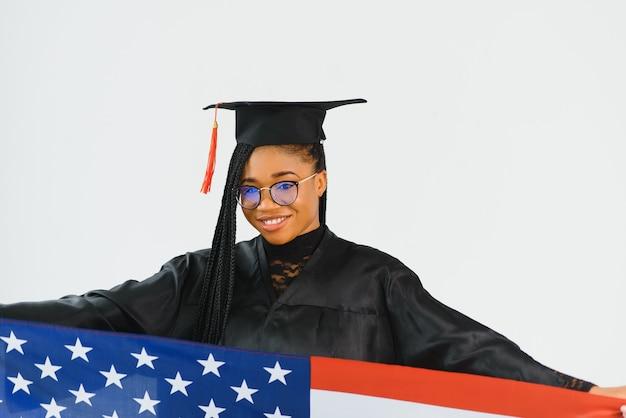 Affascinante studentessa sorridente in occhiali che indossano mantello nero e in piedi con la bandiera americana