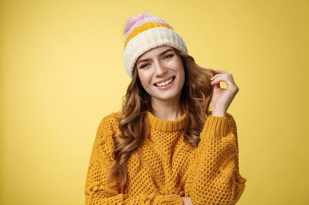 Affascinante ragazza civettuola femminile cerca un ragazzo ricco durante le vacanze invernali sulle montagne chiedi all'istruttore civettuolo insegnare lo snowboard guardando la telecamera seducente arrotolando il dito indice, sfondo giallo
