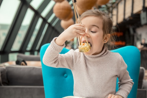 Ragazza divertente affascinante che mangia i sushi in un ristorante