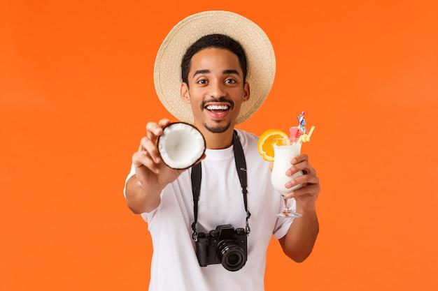 Affascinante uomo afroamericano divertente e felice, sorridente che ti dà il cocco con la mano allungata, tenendo cocktail, bevendo succo e godendo resort di lusso in viaggio all'estero, arancio