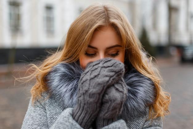 Affascinante giovane donna divertente ride e si copre il viso con le mani in guanti lavorati a maglia su edifici d'epoca. bella ragazza allegra.