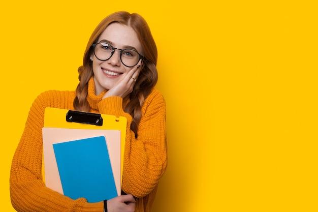 Affascinante studente caucasico di zenzero con lentiggini e occhiali è in possesso di alcuni libri e posa su una parete gialla con spazio libero