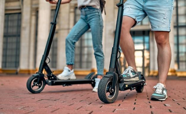 Una ragazza affascinante e un ragazzo attraente su scooter elettrici. un paio di studenti in scooter vicino al campus.