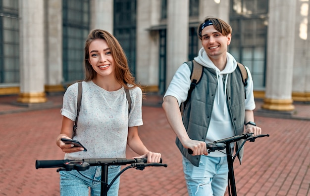 Una ragazza affascinante e un ragazzo attraente su scooter elettrici con uno smartphone.