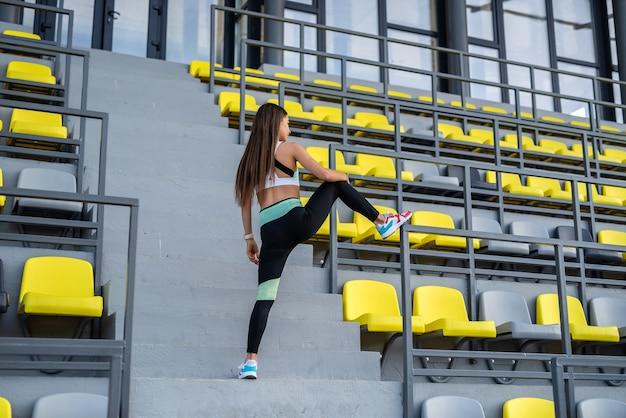 Affascinante ragazza che fa esercizi di stretching sugli spalti dello stadio per un corpo perfetto, soleggiata giornata estiva