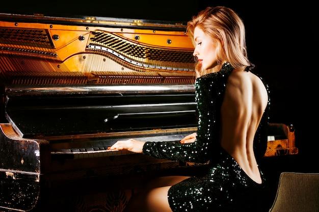 Affascinante ragazza in abito da sera in posa vicino al vecchio pianoforte tedesco