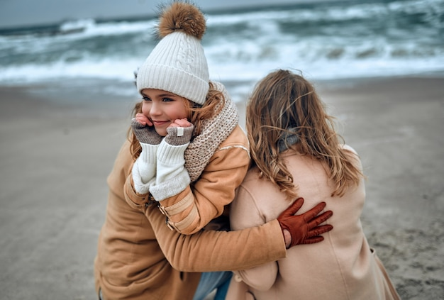 Una ragazza affascinante con un cappello lavorato a maglia e guanti con i suoi genitori si rilassa in riva al mare nella stagione fredda.