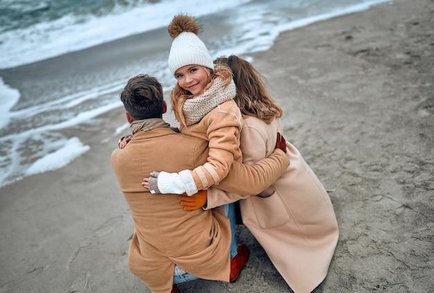 Un'affascinante ragazza con un cappello a maglia e guanti con i suoi genitori si rilassa in riva al mare in inverno.