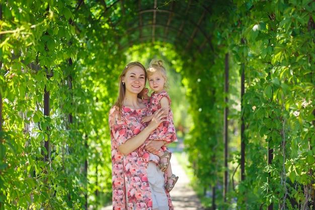 Un'affascinante ragazza in un leggero prendisole estivo cammina in un parco verde con la sua piccola figlia, tenendola tra le braccia. gode di calde giornate estive soleggiate.