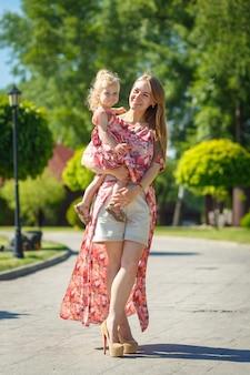 Un'affascinante ragazza in un leggero prendisole estivo cammina in un parco verde con la sua piccola figlia, tenendola tra le braccia.