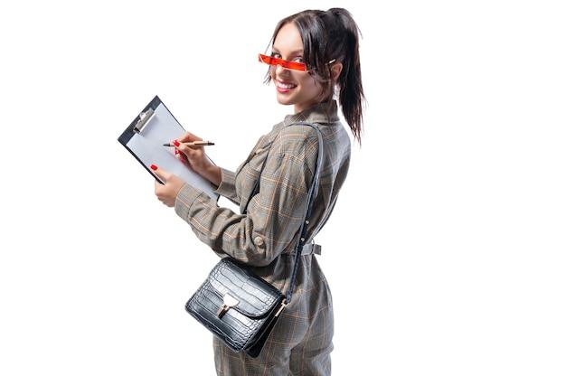 Affascinante ragazza prende appunti sulla tavoletta