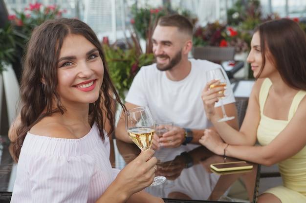 Affascinante donna felice sorridente con un bicchiere di vino in mano, divertendosi a festeggiare con i suoi amici al bar
