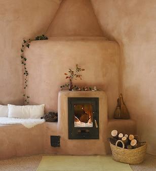 Affascinante stufa a inerzia in argilla e gesso rosa con fuoco acceso e cesto di legna